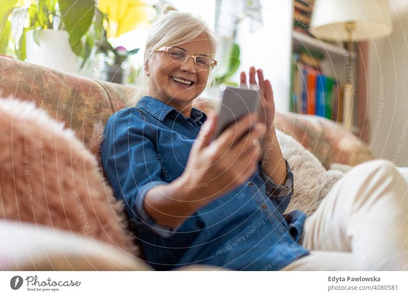 Senior woman using mobile phone at home smiling happy enjoying positivity vitality confidence people senior mature casual female Caucasian elderly house old
