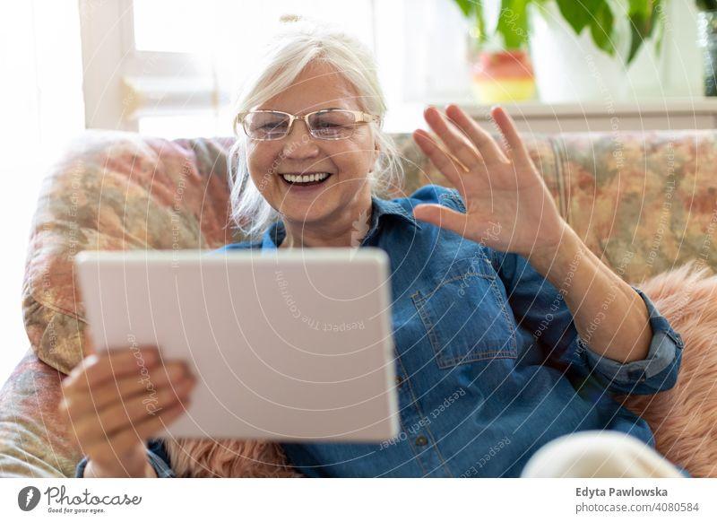 Senior woman using digital tablet at home smiling happy enjoying positivity vitality confidence people senior mature casual female Caucasian elderly house old