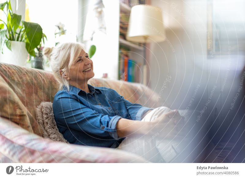 Beautiful senior woman relaxing at home smiling happy enjoying positivity vitality confidence people mature casual female Caucasian elderly house old aging