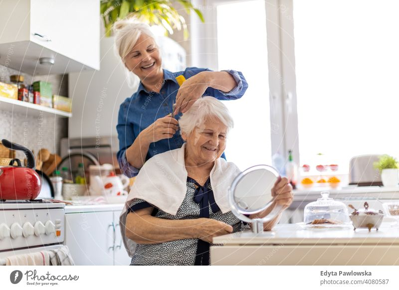 Woman cutting her elderly mother's hair at home smiling happy people woman senior mature female house old domestic life grandmother pensioner grandparent