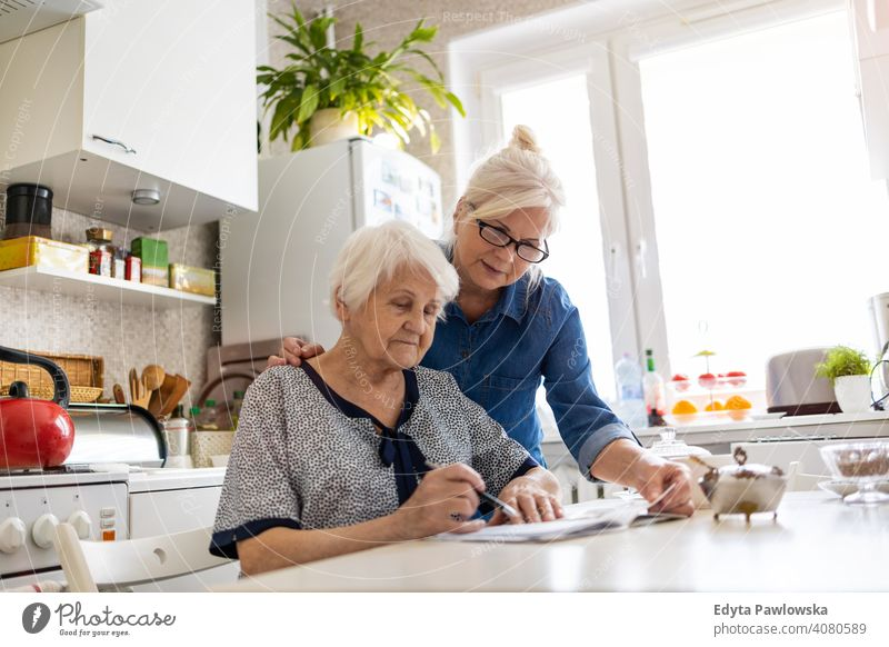 Mature woman helping elderly mother with paperwork will document discussing writing finance money confusion reading kitchen domestic assistance support