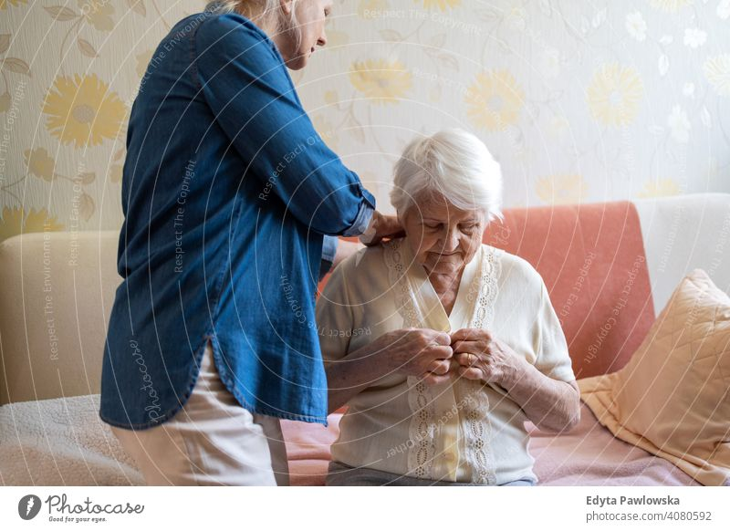 Woman helping senior woman dress in her bedroom getting dressed two people family mother daughter love together parent caregiver friendly assistance trust