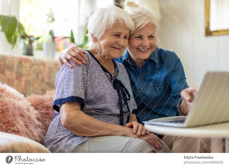 Mature daughter teaches her older mother to use the laptop Computer two persons Bonding Family Mother Daughter Love Together Visit Parents Friends kind Support