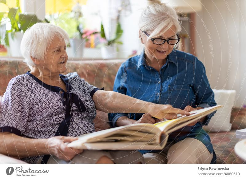 Senior woman and her adult daughter looking at photo album together on couch in living room sitting memory memories nostalgia history photos showing remember