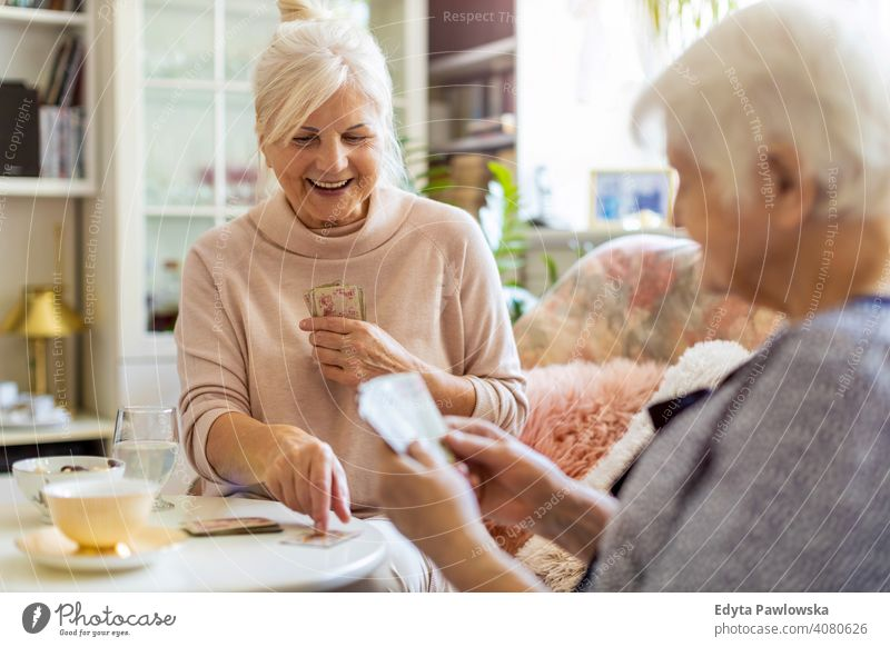 Senior woman and her adult daughter playing cards at home smiling happy enjoying positivity vitality confidence people senior mature casual female Caucasian