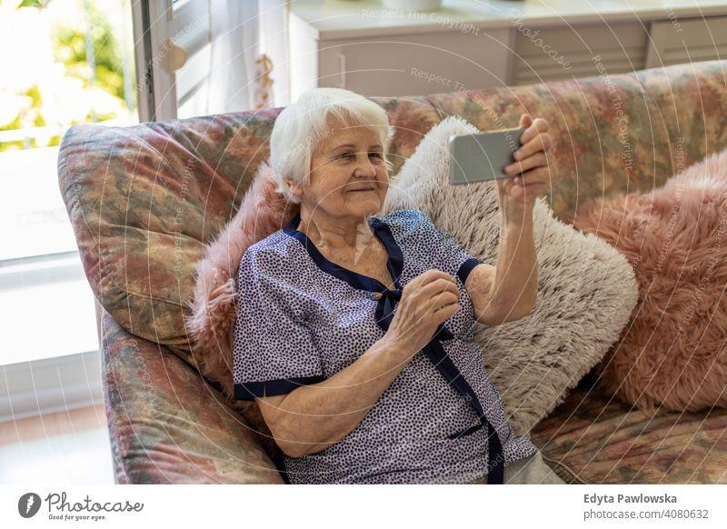 Senior woman using mobile phone at home smiling happy enjoying positivity vitality confidence people senior mature casual female Caucasian elderly house old