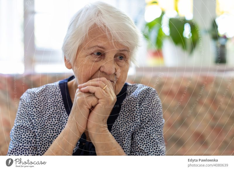 Portrait of an elderly woman in a state of worry at home sad lonely unhappy depression uncertainty anxiety worried grief sadness loss problem crisis serious