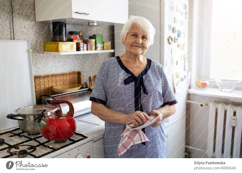 Senior woman in her kitchen drying dishes people senior mature casual female Caucasian elderly home house old aging domestic life grandmother pensioner
