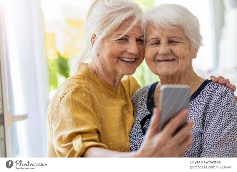 Senior woman and her adult daughter using smartphone together smiling happy enjoying positivity vitality confidence people senior mature casual female Caucasian