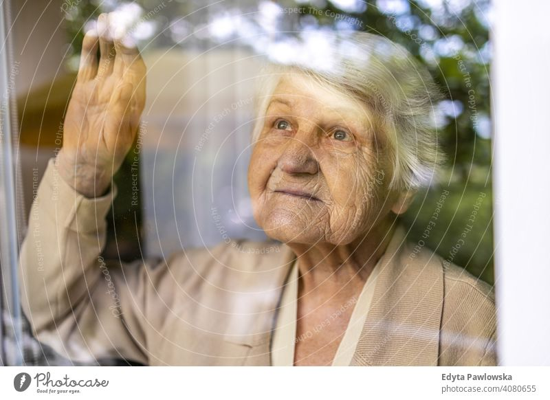 Senior woman looking out of window at home sad lonely unhappy depression uncertainty anxiety worried grief sadness loss problem crisis serious nostalgia
