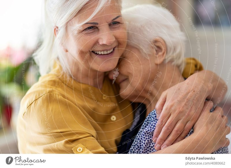 Woman hugging her elderly mother smiling happy enjoying positivity vitality confidence people woman senior mature casual female Caucasian home house old aging