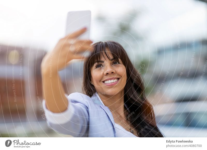 Attractive young woman using smartphone in the city hispanic latin smiling summer fun joy happy happiness urban girl people female lifestyle outdoors adult