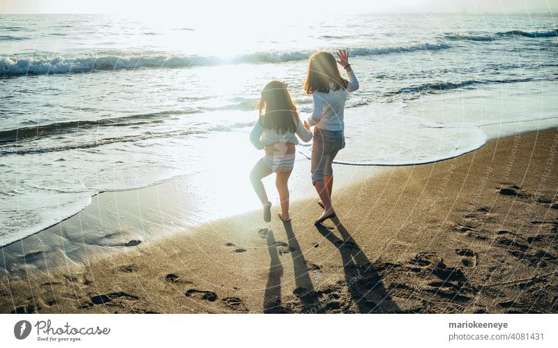 Back view of two little girls holding hands in front of the sea on a sunny afternoon. Concept of friendship two people horizontal togetherness females children