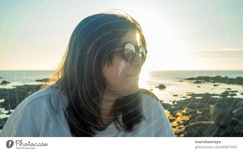 Side close-up of a Caucasian woman wearing sunglasses during a sunset by the sea close up caucasian one woman only lifestyle color image copy space sunshine