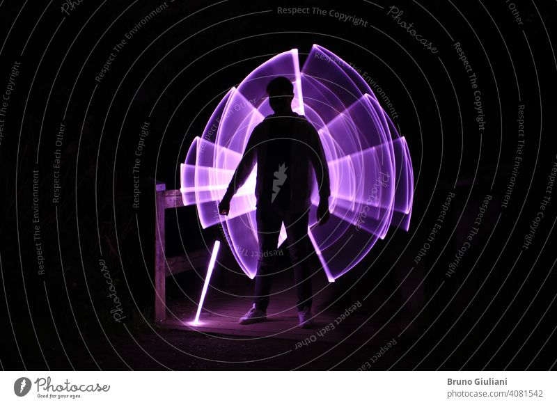 Silhouette of a man standing with a lightsaber with neon drawings and leds at lightpainting boy abstract illustration silhouette energy sphere concept purple