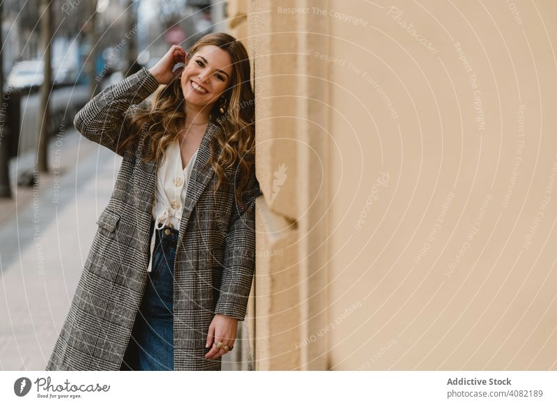 Woman leaning on wall on street woman building laughing city young cheerful style female urban trendy fun joke joy happy casual elegant exterior lady structure