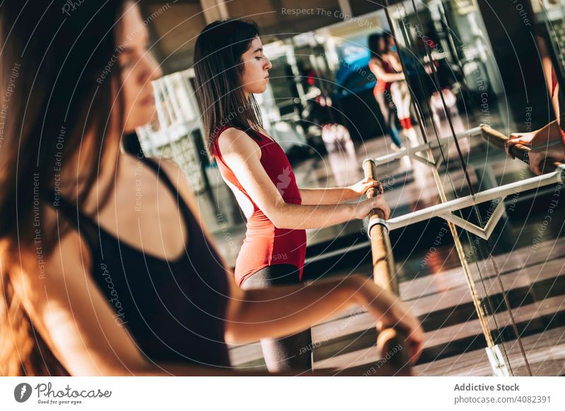 Young ballet dancer working out in studio women barre stretching dancers lesson mirror training confident sunlight dancing unemotional athletic gymnastics