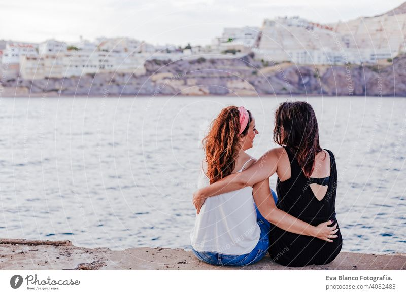 two women friends sitting by the beach hugging. lifestyle concept outdoors casual gay urban cheerful girlfriend standing couple young affection woman people