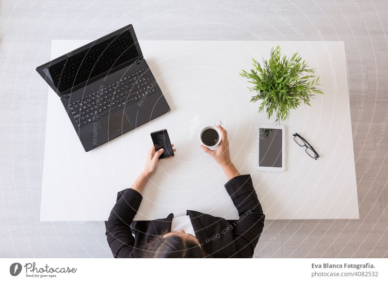 top view of a young business woman working at the office with mobile phone and holding a cup of coffee. Daytime. Lifestyles. Indoors computer laptop worker