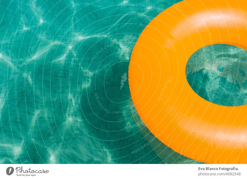 orange inflatable donut on blue water in a swimming pool. Summer fun summer party summertime beautiful float female leisure relax background ring sunny holiday