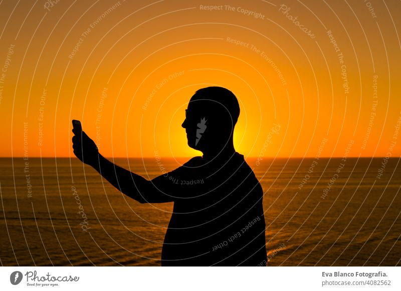 silhouette of a young man using mobile phone at sunset. Ocean background. Vacation and technology concept hand cell telephone person tourist people mountain