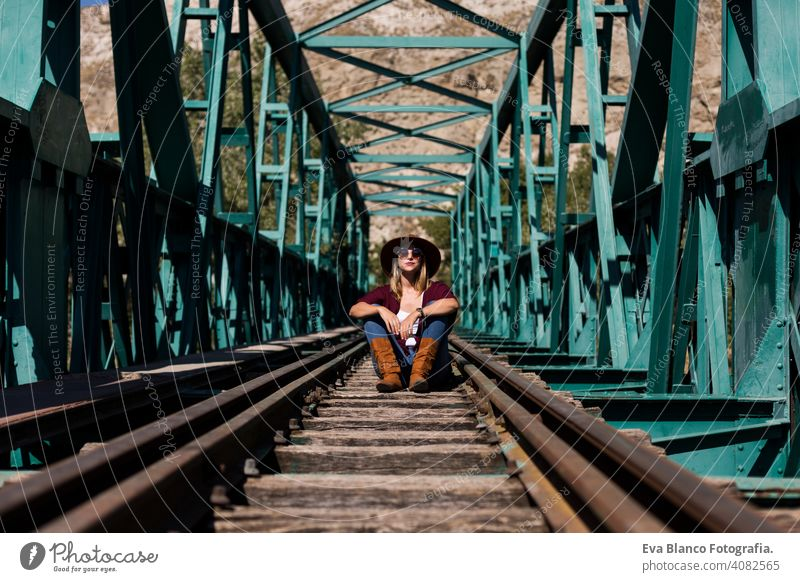 portrait of a young beautiful woman sitting on the railway of a green bridge. Wearing stylish clothes and a hat. LIfestyle. Outdoors. Sunny train female pretty