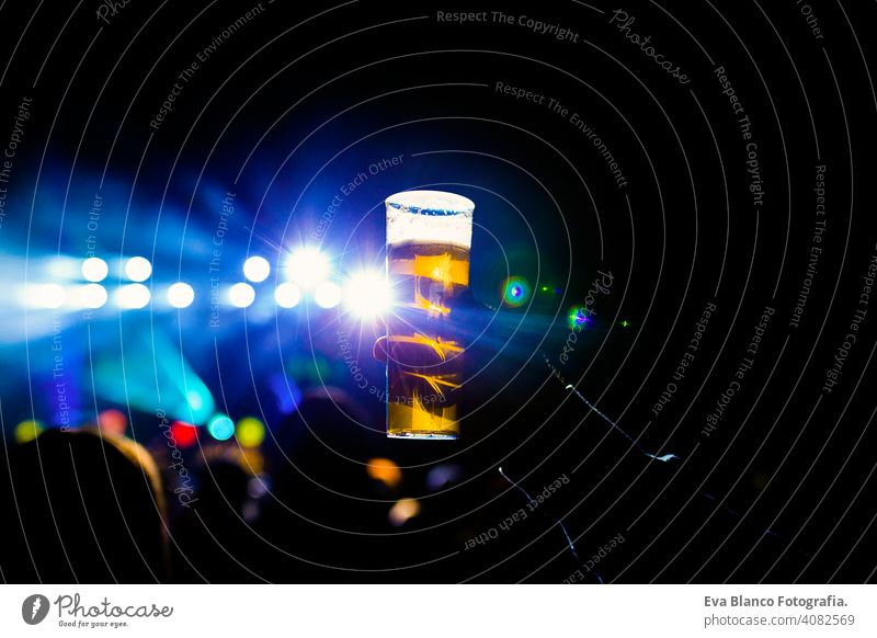 man holding glass of beer in a night concert. Unrecognizable crowd background. blue lights fan people live performer happy music mobile phone dance young