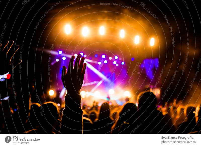 Picture of a lot of people enjoying night perfomance, large unrecognizable crowd dancing with raised up hands and mobile phones on concert. nightlife fan live