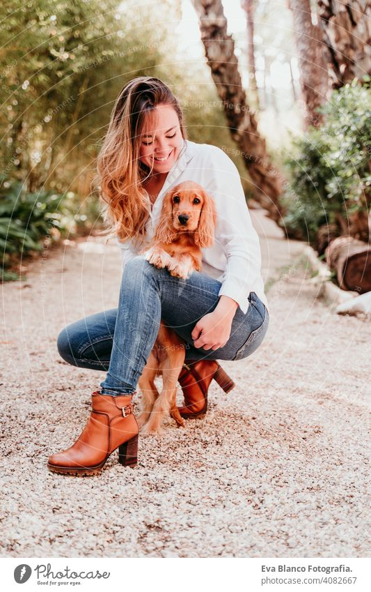 young woman and her cute puppy of cocker spaniel outdoors in a park dog pet sunny love hug smile kiss breed purebred beautiful blonde brown lifestyle portrait