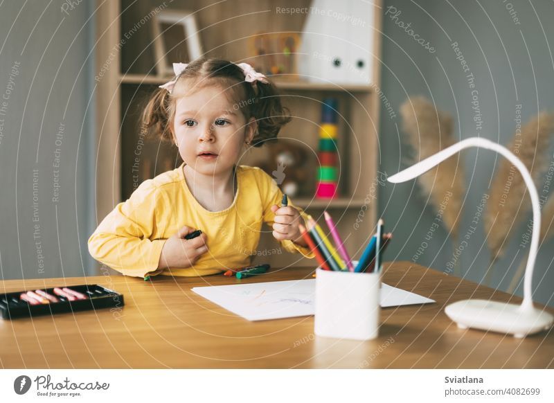 A little girl draws at the table with colored pencils at home or in kindergarten. Childhood, creativity, education. paper cute desk child kid childhood