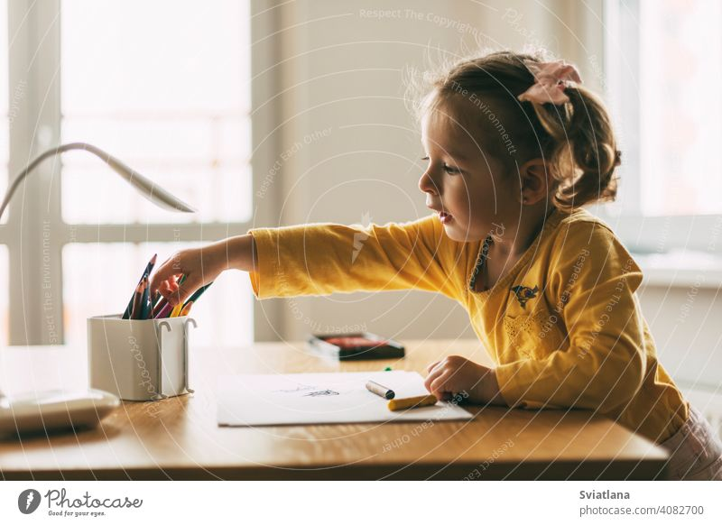 A little girl draws at the table with colored pencils at home or in kindergarten. Childhood, creativity, education. Side view paper cute desk child kid