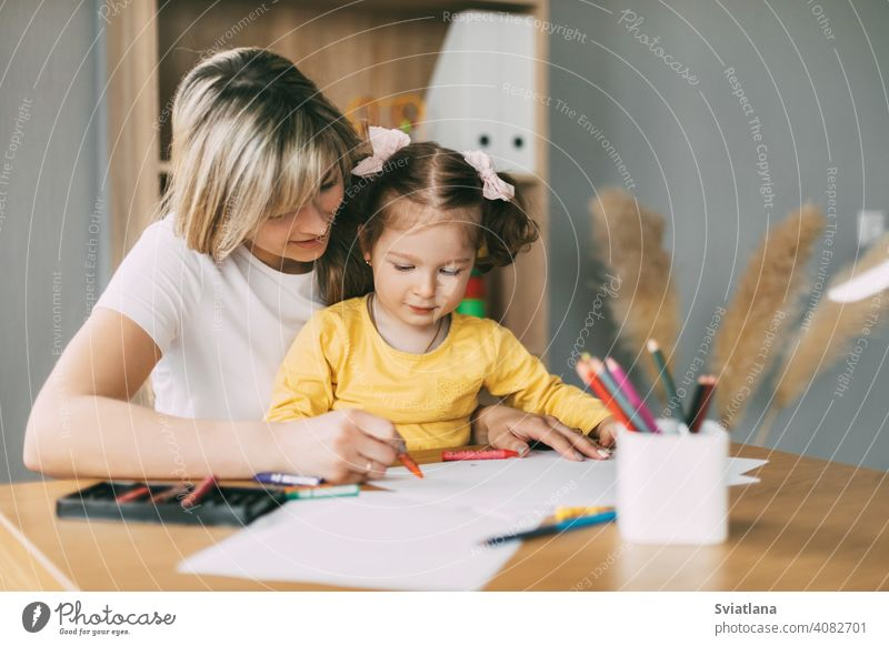 Happy mother and daughter draw together with colored pencils at the table in the room. Time together, creativity, education girl child mom drawing paint paper