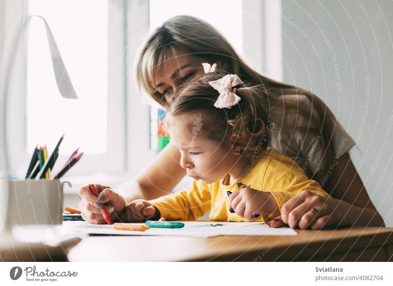 A young mother teaches her little daughter to draw with colored pencils. Time together, creativity, education. Side view girl child mom drawing paint table