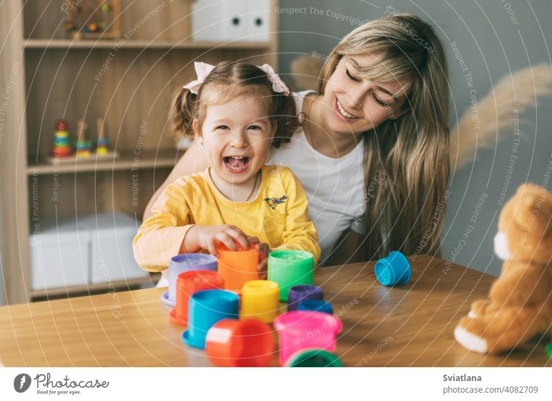 Mom and a laughing little girl play with colorful molds at the table at home. Time together, motherhood, parenthood child game build pyramid preschool mom