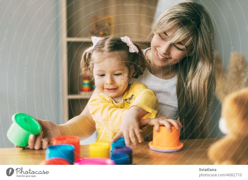 Mom and a laughing little girl play with colorful molds at the table at home. Time together, motherhood, parenthood child game preschool mom learning cute