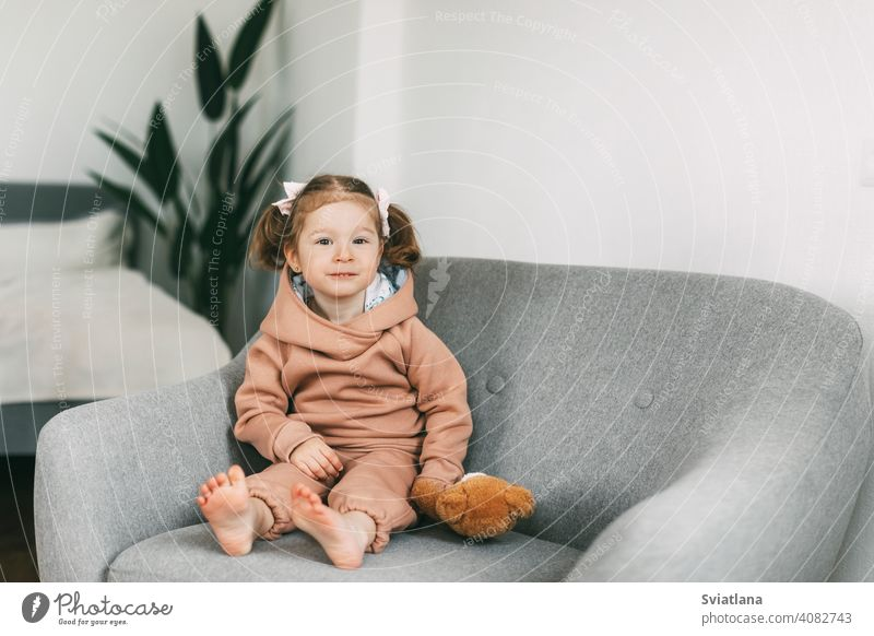 A little charming girl sits in a chair with her toy bear and smiles small kid cute sitting child childhood teddy bear happy fun adorable beautiful young one