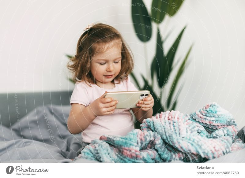 A little girl watches cartoons on her phone or plays on the bed before going to bed smartphone child kid mobile home small communication looking bedtime people