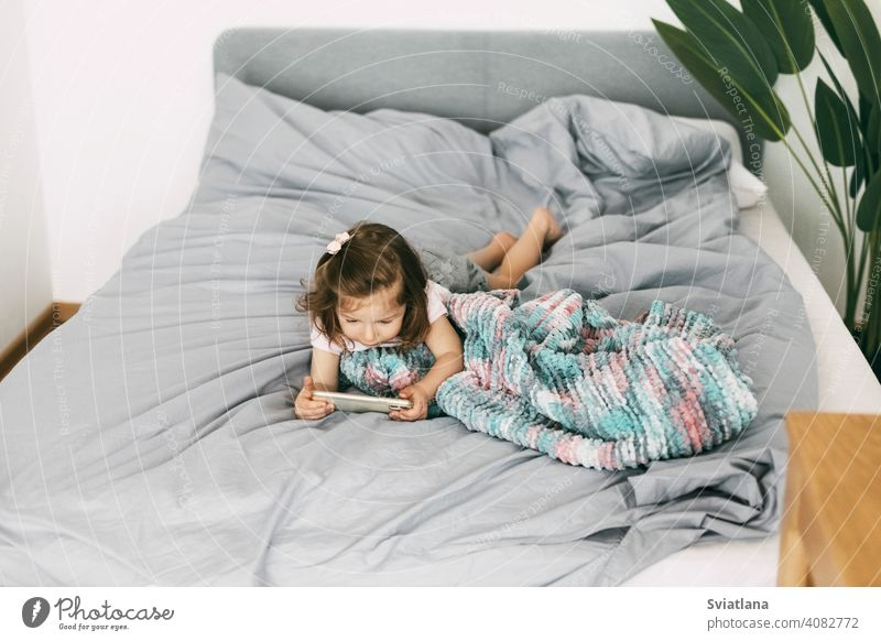 A little girl watches cartoons on her phone or plays on the bed before going to bed. Top view smartphone child kid mobile home small communication looking