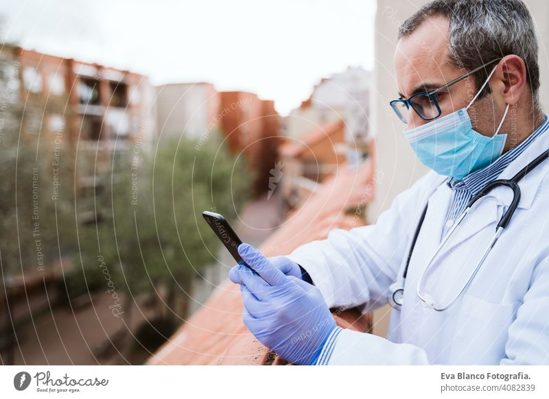 doctor man taking a break, using mobile phone. Wearing protective gloves, mask and stethoscope. coronavirus covid-19 concept corna virus protective mask