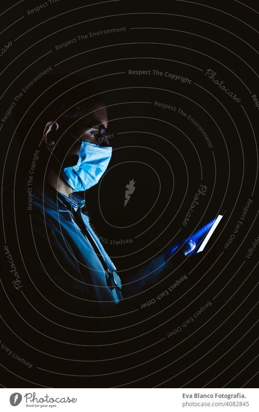 doctor man indoors, using mobile phone. Wearing protective gloves, mask and stethoscope. coronavirus covid-19 concept internet tecgnology dark corna virus