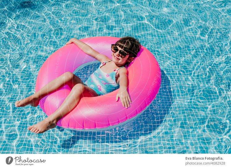 beautiful kid girl floating on pink donuts in a pool. Wearing sunglasses and smiling. Fun and summer lifestyle activity beauty outdoor teenager swimming