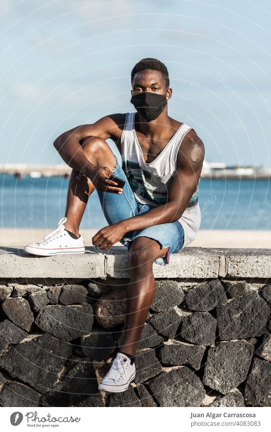 Black man in mask and with smartphone on seashore seaside beach protect summer mobile male ethnic black african american lanzarote spain stone fence serious sit