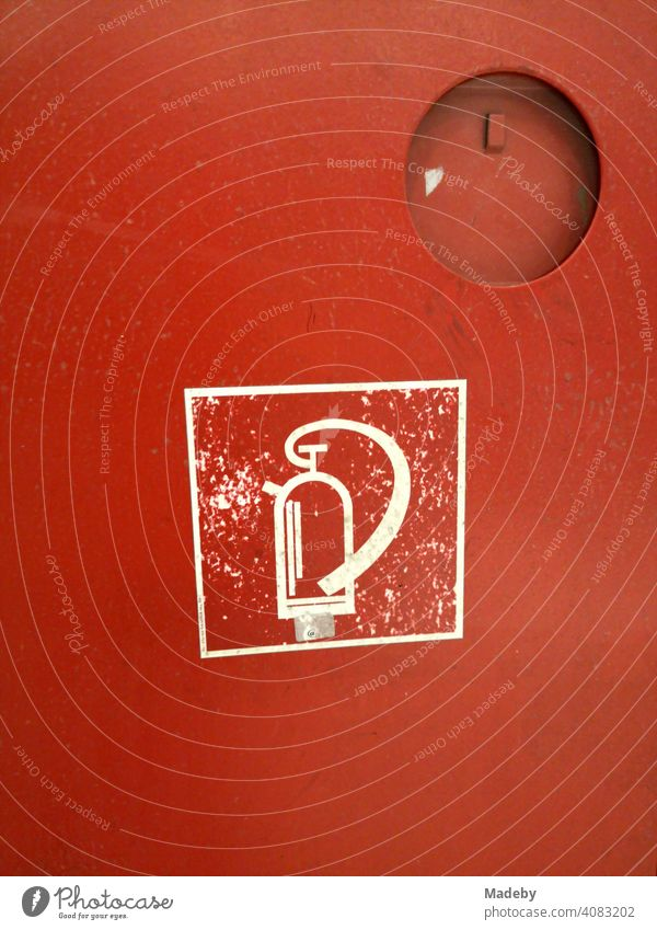 Symbol of a fire extinguisher in white on the red fireproof metal cabinet in the subway station Bochenheimer Warte in the district of Bockenheim in Frankfurt am Main, Germany
