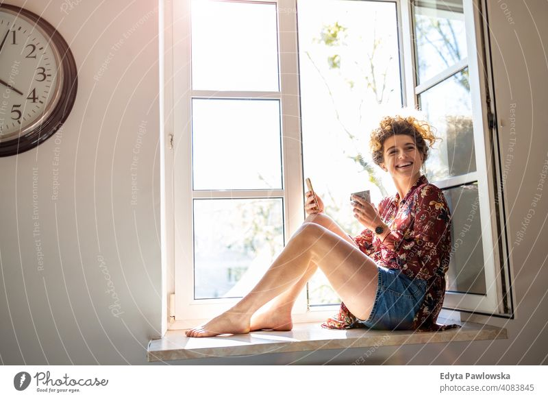 Young woman sitting on window sill and using smartphone happy smiling cheerful apartment leisure bedroom house home alone people caucasian adult indoors person