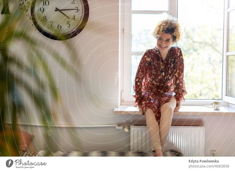 Relaxed woman at home sitting at the window happy smiling cheerful apartment leisure bedroom house alone people caucasian adult indoors person casual attractive