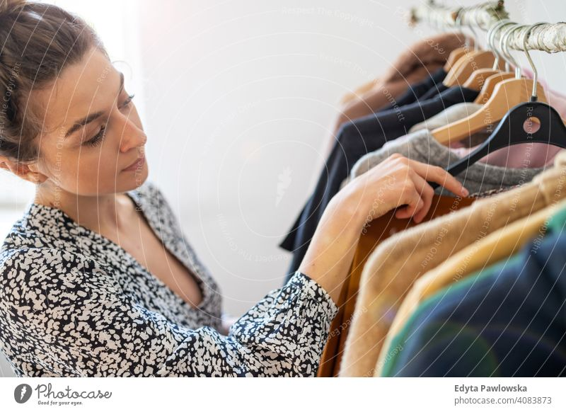 Young woman shopping at a clothing boutique fashion clothes fashionable rack choosing retail store sale hanger customer style shopper shopaholic wardrobe choice