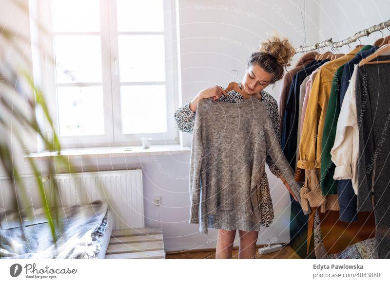 Young woman choosing clothes fashion clothing fashionable rack retail store shop sale hanger customer style shopper shopaholic wardrobe choice buy dress