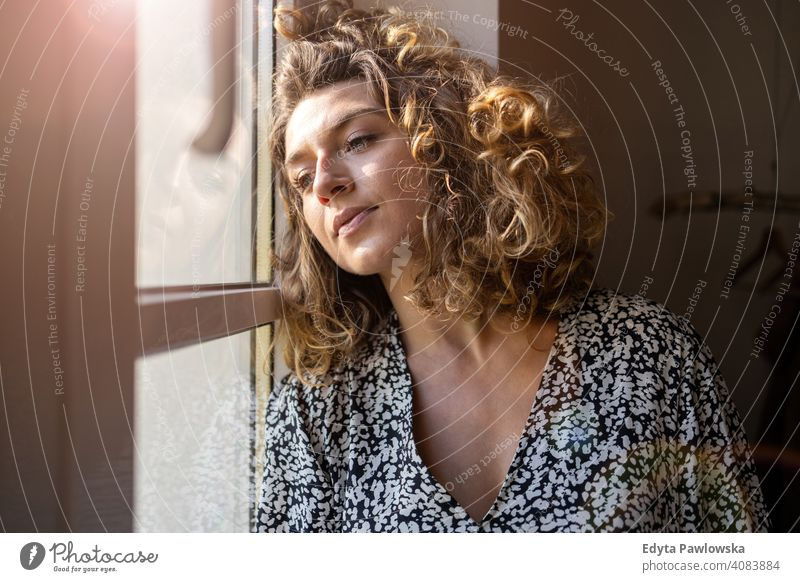 Young woman looking out of window lockdown stay at home covid coronavirus pandemic quarantine social distancing illness epidemic infection safety covid-19