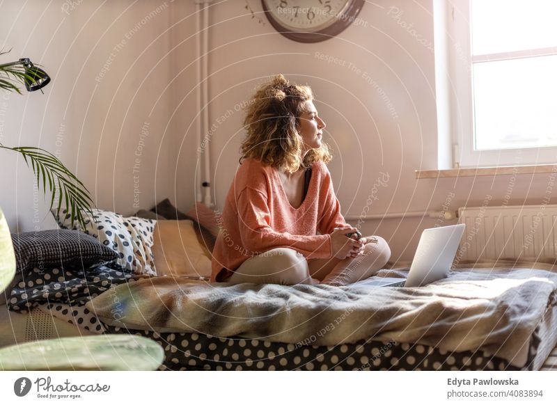 Young woman working in bed at home with laptop education learning studying homework book e-learning technology computer internet online communication wireless