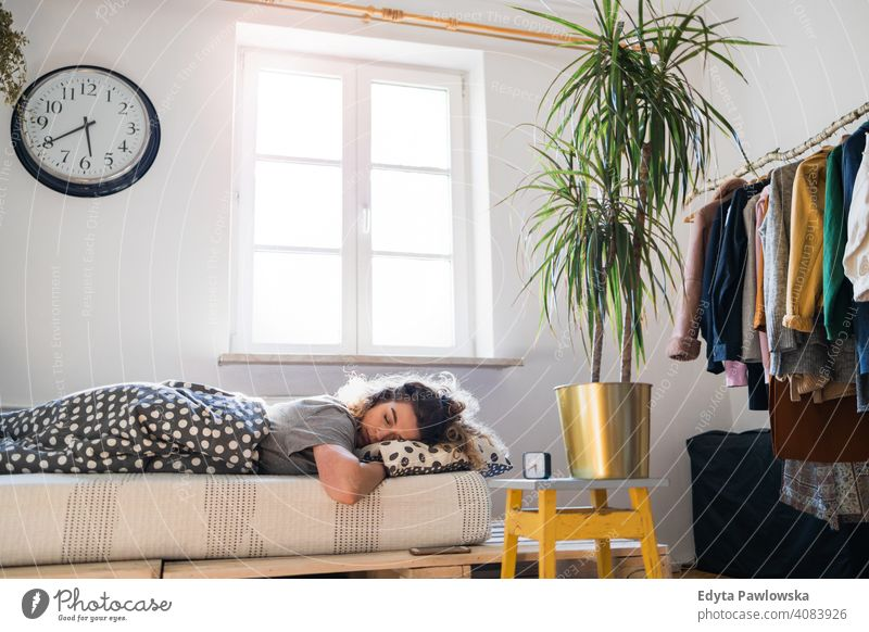 Young woman asleep in bed morning clock resting relaxation sleeping awake alarm clock sleepy waking up apartment leisure bedroom house home alone people